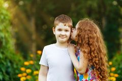 Friends boy and girl embracing and whispers in spring park. Royalty Free Stock Images