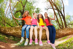 Cute friends having fun on fallen tree stem royalty free stock photo