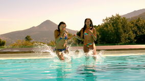 Cute friends jumping into swimming pool together stock video