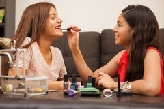 Cute friends putting lipstick on Royalty Free Stock Photos