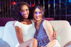 Cute friends sitting on a couch. In a nightclub Royalty Free Stock Image
