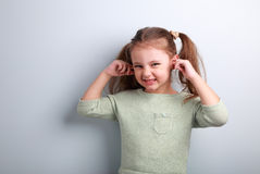 Cute fun kid girl coverd ears the fingers and gesturing that don Royalty Free Stock Images