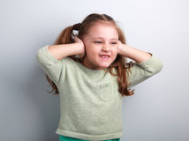 Cute fun kid girl coverd ears the fingers and gesturing that not Royalty Free Stock Images