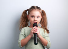 Cute fun kid girl singing song in microphone on blue background. Royalty Free Stock Photography