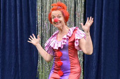 Cute fun redhead performer in a red clowns nose. And brightly colored costume bending forwards waving at the camera with a vivacious grin Royalty Free Stock Photo