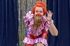 Cute fun redhead performer in a red clowns nose. And brightly colored costume bending forwards waving at the camera with a vivacious grin Royalty Free Stock Images