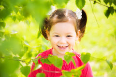 Cute funny active girl. Closeup portrait of cute funny laughing girl of four years old playing cheerfully outside in spring sunny city park. Horizontal color Stock Photography
