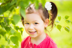 Cute funny active girl. Closeup portrait of cute funny laughing girl of four years old playing cheerfully outside in spring sunny city park. Horizontal color Royalty Free Stock Photography