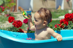 Cute funny baby boy bathing outdoor among flowers. Cute funny baby boy bathing outdoor on green lawn among flowers Stock Image