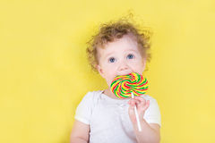 Cute funny baby girl with a big candy. Cute funny little baby girl with a big candy on yellow background Stock Photos