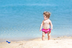 Cute funny baby girl with curly hair in sand on beach Royalty Free Stock Photography