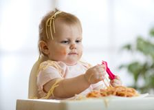 Cute funny baby girl eating spaghetti at home. Funny baby girl eating spaghetti at home Stock Photography