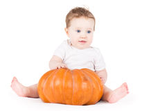 Cute funny baby girl playing with a big pumpkin Stock Image