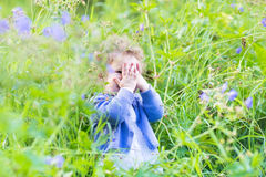 Cute funny baby girl playing hide and seek. Cute funny little baby girl playing hide and seek in the garden Royalty Free Stock Photography