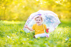 Cute funny baby girl playing in rain under umbrella Royalty Free Stock Image