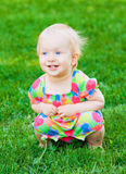 Cute funny baby girl sitting on grass Stock Image