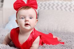 Cute funny baby in red dress and bow is on bed. With pillows in bedroom Stock Photography