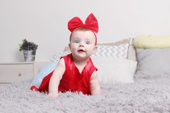 Cute funny baby in red dress and bow crawls on bed. With pillows in bedroom Royalty Free Stock Images