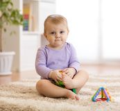 Cute funny baby sitting on carpet at home stock photo