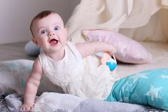 Cute funny baby in white dress plays with toy. On floor with pillows in room Stock Images