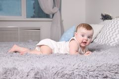 Cute funny baby in white lies on bed with pillows. In bedroom Royalty Free Stock Photos