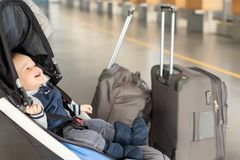 Cute funny caucasian baby boy sitting in stroller near luggage at airport terminal. Child sin carriage with suitcasese royalty free stock photos