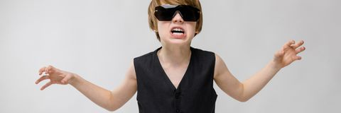 Portrait of adorable funny little boy standing in studio with sunglasses showing agression anger wanting to scratch on. Cute funny caucasian little boy in black royalty free stock photo
