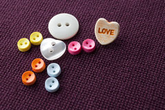 Cute funny character with love heart. Colorful sewing buttons hero on violet textile background. Valentines day concept Royalty Free Stock Photography