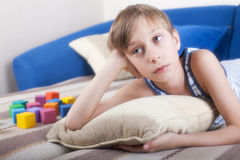 Cute funny child resting on a cozy sofa with colorful toys. (cubes) and pilows Stock Images