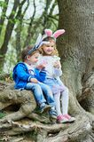 Cute funny girl and boy with Easter eggs at park. easter concept. Children playing with easter eggs on Easter day stock photo