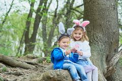 Cute funny girl and boy with Easter eggs at park. easter concept. Children playing with easter eggs on Easter day royalty free stock images
