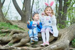 Cute funny girl and boy with Easter eggs at park. easter concept. Children playing with easter eggs on Easter day stock photos