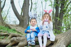 Cute funny girl and boy with Easter eggs at park. easter concept. Children playing with easter eggs on Easter day stock images