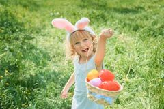 Cute funny girl with Easter eggs and bunny ears at garden. easter concept. Laughing child at Easter egg hunt. Cute funny girl with bunny ears at garden. easter royalty free stock images