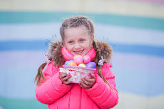 Cute funny girl with colored eggs in the basket for Easter Royalty Free Stock Images