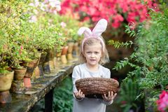 Cute funny girl with Easter bunny ears at garden. easter concept. Laughing child at Easter egg hunt stock image