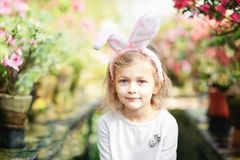 Cute funny girl with Easter bunny ears at garden. easter concept. Laughing child at Easter egg hunt. Baby caucasian celebrate celebration cheerful colorful stock photos
