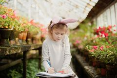 Cute funny girl with Easter bunny ears at garden. easter concept. Laughing child at Easter egg hunt. Girl draws easter egg on paper sheet. Child paint eggs stock photography