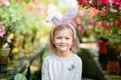 Cute funny girl with Easter bunny ears at garden. easter concept. Laughing child at Easter egg hunt. Baby caucasian celebrate celebration cheerful colorful royalty free stock photos
