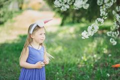 Cute funny girl with Easter eggs and bunny ears at garden. easter concept. Laughing child at Easter egg hunt. Baby caucasian celebrate celebration cheerful royalty free stock images