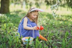 Cute funny girl with Easter eggs and bunny ears at garden. easter concept. Laughing child at Easter egg hunt royalty free stock images