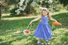 Cute funny girl with Easter eggs and bunny ears at garden. easter concept. Laughing child at Easter egg hunt. Baby caucasian celebrate celebration cheerful stock photography