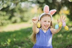Cute funny girl with Easter eggs and bunny ears at garden. easter concept. Laughing child at Easter egg hunt stock images