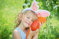 Cute funny girl with Easter eggs and bunny ears at garden. easter concept. Laughing child at Easter egg hunt. Child in park with basket full of eggs, spring royalty free stock image