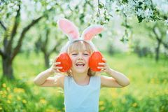 Cute funny girl with Easter eggs and bunny ears at garden. easter concept. Laughing child at Easter egg hunt. Child in park with basket full of eggs, spring royalty free stock photos