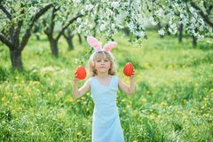 Cute funny girl with Easter eggs and bunny ears at garden. easter concept. Laughing child at Easter egg hunt. Child in park with basket full of eggs, spring stock images