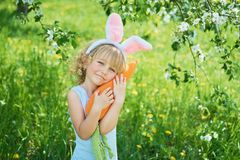 Cute funny girl with Easter eggs and bunny ears at garden. easter concept. Laughing child at Easter egg hunt. Child in park with eggs, spring concept baby stock photos