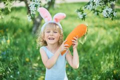 Cute funny girl with Easter eggs and bunny ears at garden. easter concept. Laughing child at Easter egg hunt. Child in park with eggs, spring concept baby royalty free stock photography