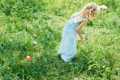 Cute funny girl with Easter eggs and bunny ears at garden. easter concept. Laughing child at Easter egg hunt. Child in park with basket full of eggs, spring royalty free stock images
