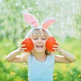 Cute funny girl with Easter eggs and bunny ears at garden. easter concept. Laughing child at Easter egg hunt. Child in park with basket full of eggs, spring stock image